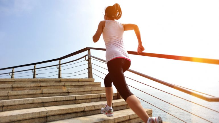 Runner athlete running at seaside stone stairs. woman fitness jogging workout wellness concept.