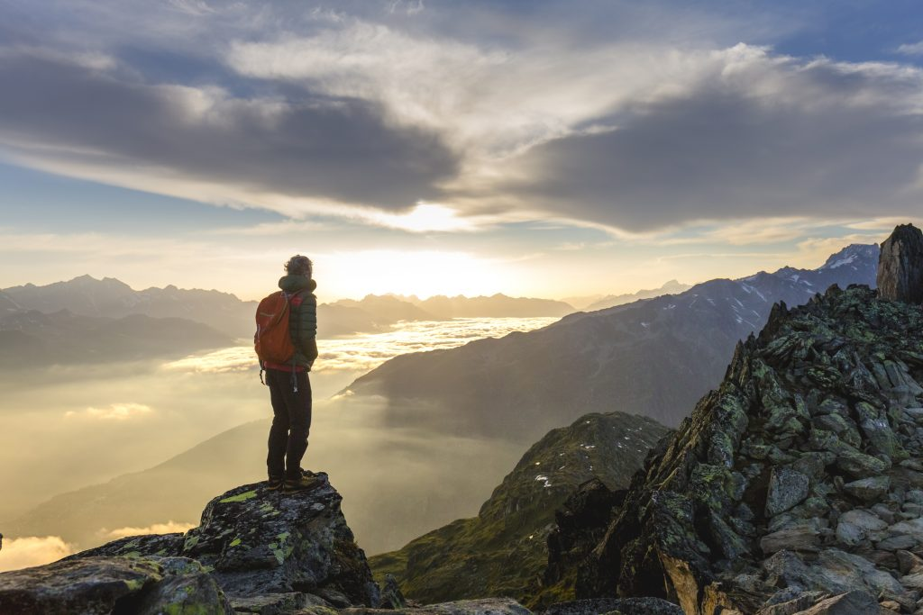 Hiker on mountain enjoying the view as metaphor for Central Bank Digital Currency and its impact on the banking system