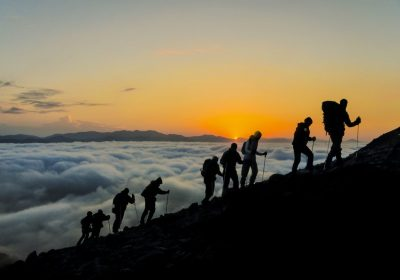 Silhouettes of hikers climbing the mountain at sunset as a metaphor for employee activation