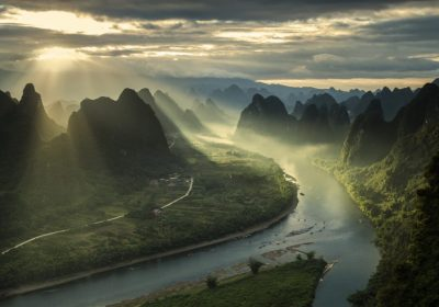 Sun beams on a misty morning on karst mountains and river
