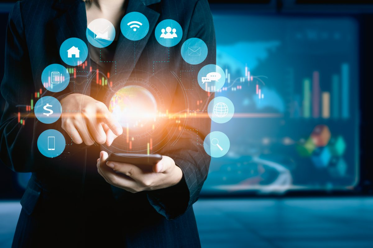 """Businesswomen using mobile phone analyzing data and economic growth graph chart. Technology digital marketing and network connection as metaphor """"ecosystems in corporate banking"""""""