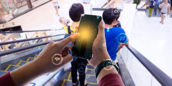 """Business person hand holding mobile phone with icons. concept of business and technology communication in the network. as metaphor for """"Platform economy—BACK to innovation in banking"""""""