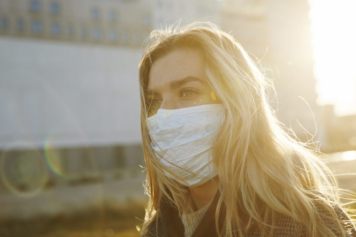 """Young woman outside wearing a virus protective face mask as metaphor for the article """"COVID-19 still looming large"""""""