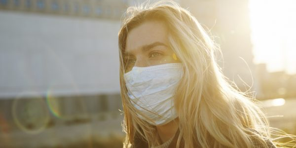 "Young woman outside wearing a virus protective face mask as metaphor for the article ""COVID-19 still looming large"""
