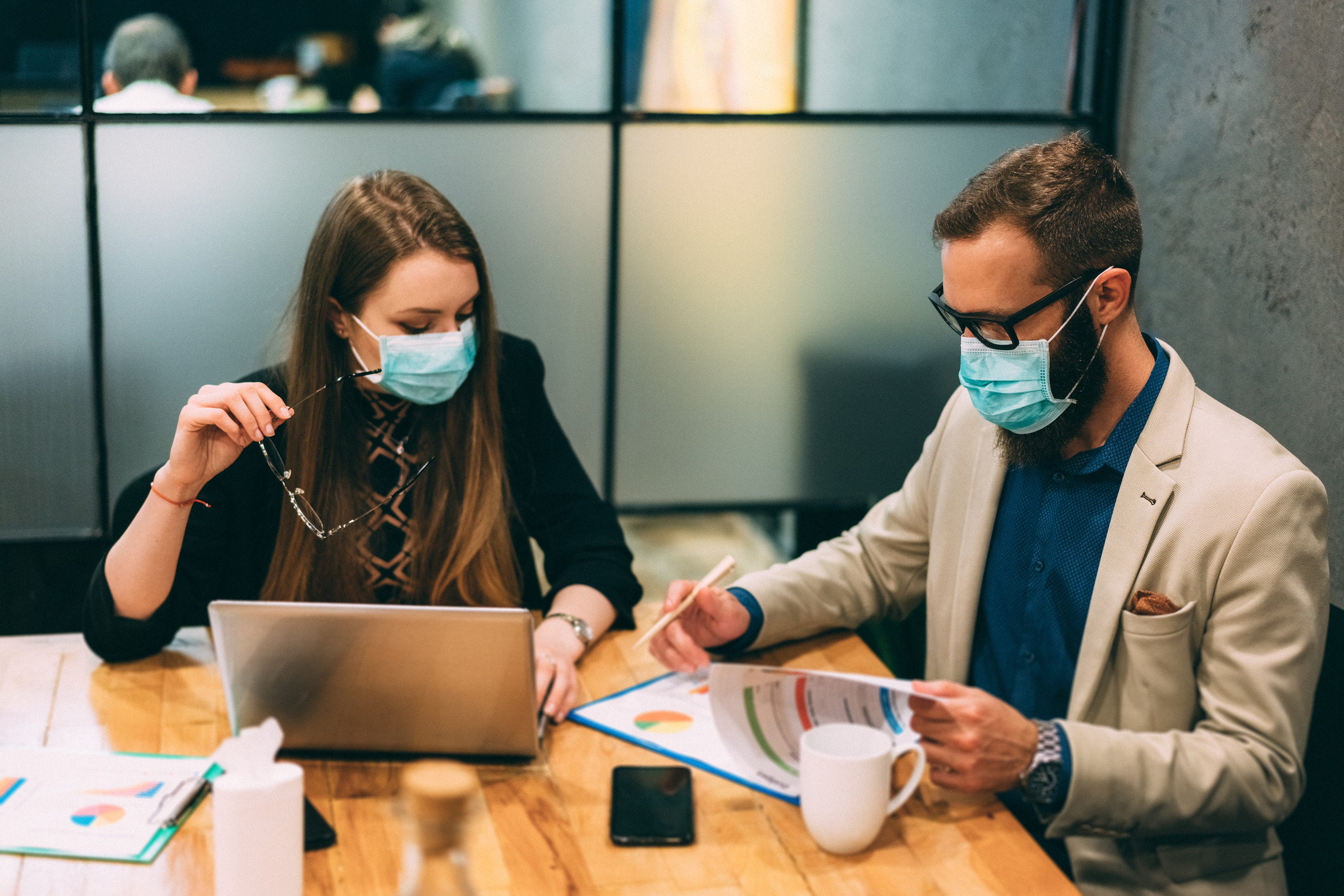Businesspeople at work during COVID-19 pandemic as metaphor for The COVID-19 impact on banks' costs