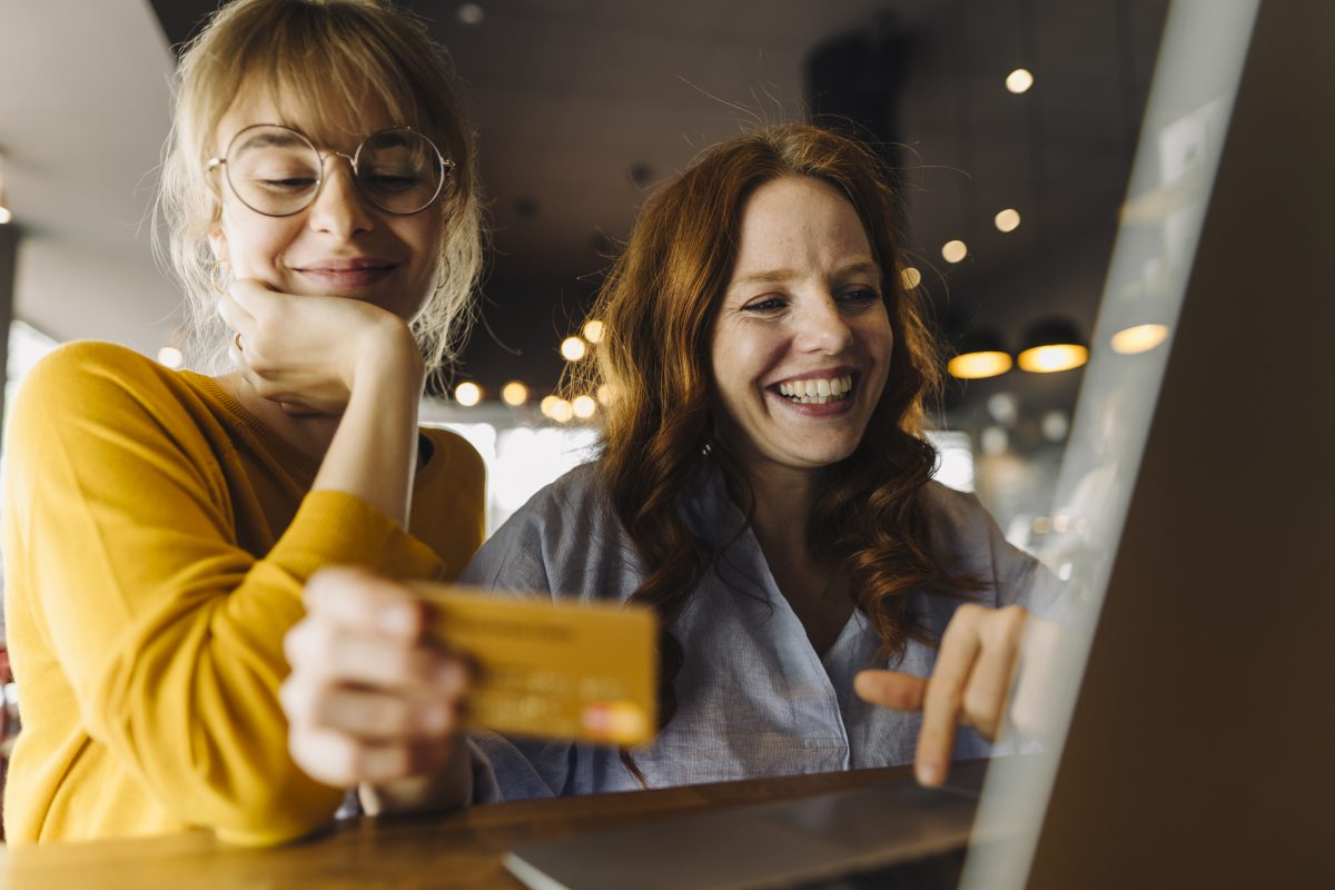 """Two happy female friends with laptop and credit card as metaphor for the article """"Payments – Made in Germany """"Payments – Made in Germany"""""""